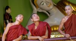 Monges na varanda do templo budista Schwedagon Temple, em frente de um buda reclinado em Yangon, Myanmar, 17 de abril de 2004. EPA/UDO WEITZ - LUSA