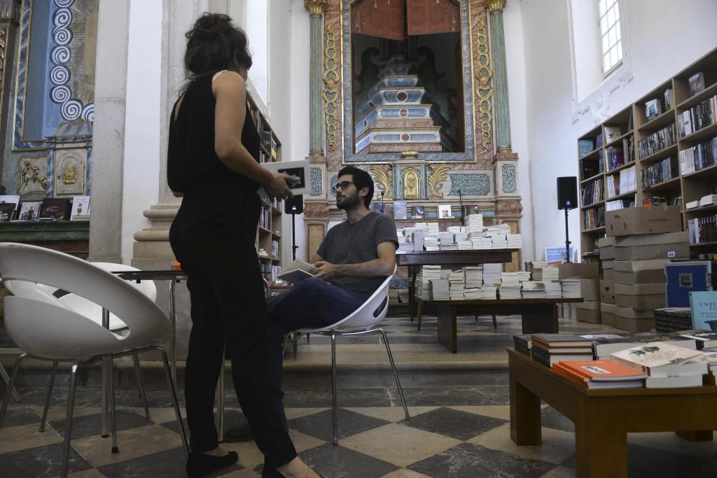 """Visitantes do Folio – Festival Internacional de Literatura de Óbidos observam livros na Igreja de S. Tiago que foi em, 2011, transformada numa livraria recheada com 40 mil obras, acondicionadas em estantes, na grande maioria redondas, criadas especialmente para acolher os livros, naquele local, Óbidos, 15 de outubro de 2015. Começou hoje o """"Folio"""" Festival Internacional de Literatura de Óbidos, onde vários espaços são transformados em livrarias. CARLOS BARROSO/LUSA"""