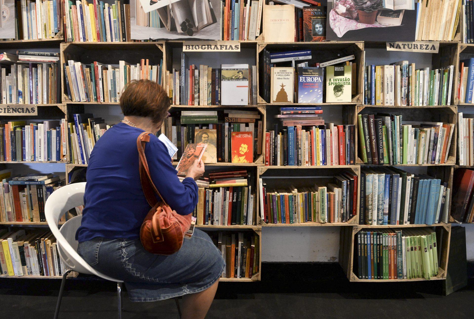 """Uma visitante do Folio – Festival Internacional de Literatura de Óbidos observa livros no mercado transformado em alfarrabista generalista, onde os livros estão guardados em """"mil caixas de fruta, colocadas nas paredes do edifício"""", Óbidos, 15 de outubro de 2015. Começou hoje o """"Folio"""" Festival Internacional de Literatura de Óbidos, onde vários espaços são transformados em livrarias. CARLOS BARROSO/LUSA"""