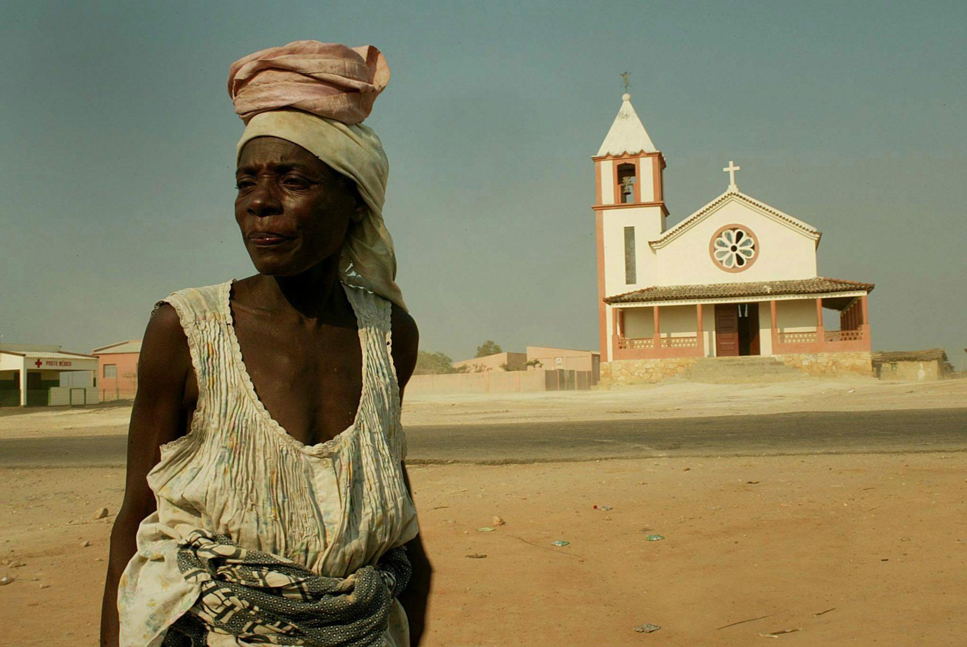 Mulher passa diante da velha igreja de Porto Quipiri na província de Bengo, Angola 24 de maio de 2004.   EPA/KIM LUDBROOK