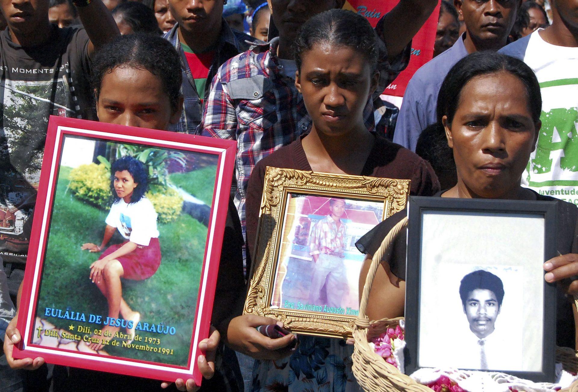 Timorenses seguram fotografias de vitimas do massacre de Santa Cruz, 12 novembro 2011, em Dili.Milhares de pessoas marcharam hoje entre a igreja de Motael e o cemitério de Santa Cruz em Díli para assinalar o vigésimo aniversário do massacre perpetrado por militares indonésios contra timorenses, provocando centenas de mortos e feridos. ANTONIO AMARAL/LUSA