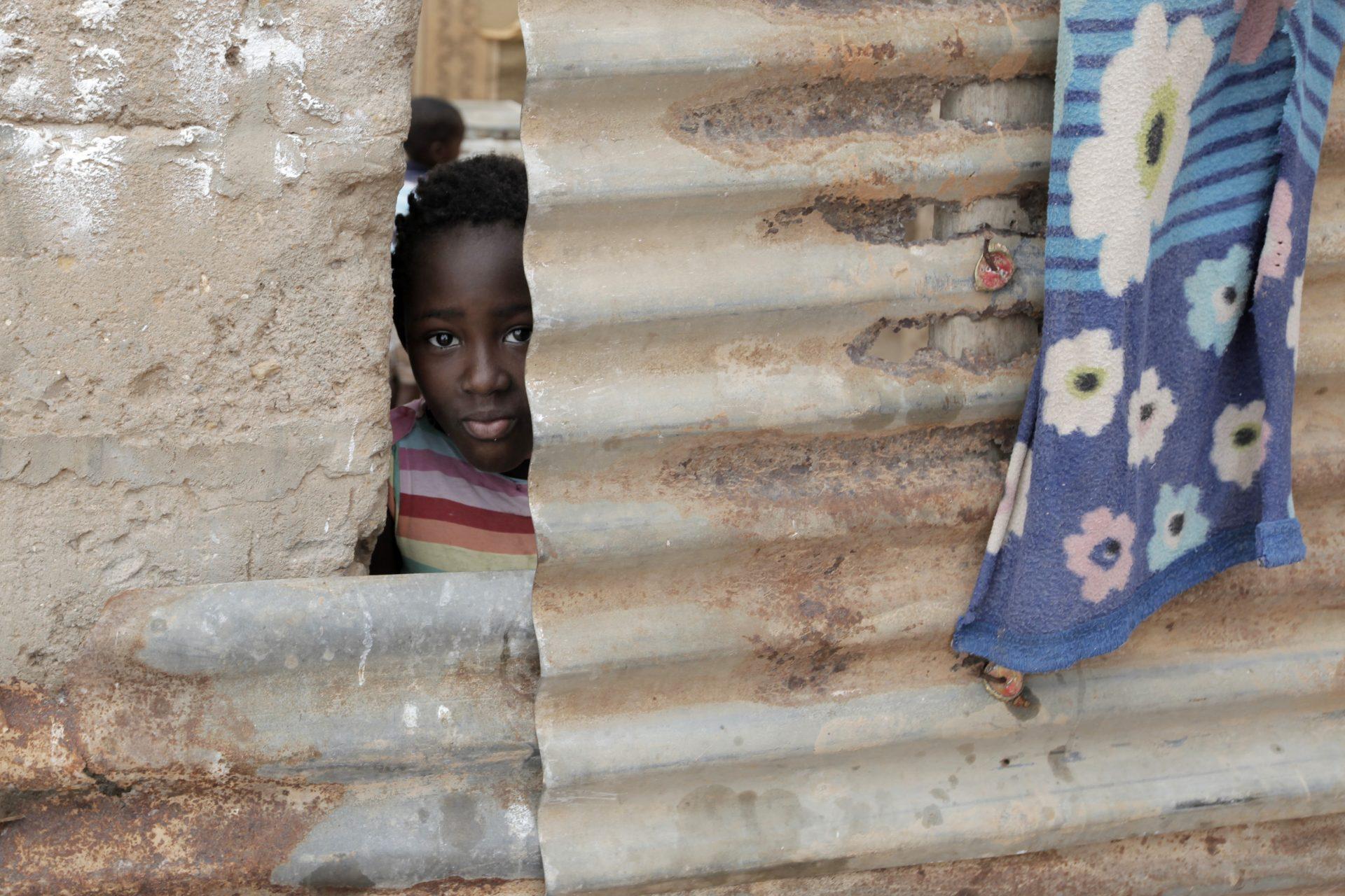 Uma criança espreita através das chapas de zinco usadas na construção de sua casa, no musseque de Zamba 2 que se estende até à cidade de Luanda, 2 novembro de 2015. Luanda é a capital de Angola, tem cerca de 6 milhões de habitantes a maior parte da população vive em bairros periféricos à cidade que é uma das cidades mais caras do mundo. PAULO CUNHA/LUSA