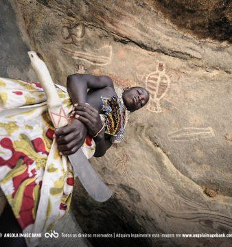 [PT] Fotografia de um Mucubal adolescente posando para a foto, fingindo que é o guardião das pinturas rupestres que se encontam nesta caverna no deserto do Namibe. Província do Namibe, Angola