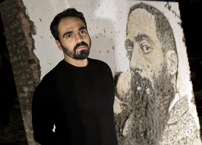 O artista Alexandre Farto, conhecido como Vhils posa para foto depois da inauguração de um mural com uma imagem do poeta Camilo Pessanha no jardim do Consulado de Portugal em Macau, cidade onde o poeta viveu e morreu, 9 de dezembro de 2016, Macau. (ACOMPANHA TEXTO) CARMO CORREIA/LUSA
