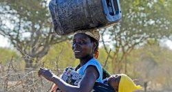 Uma mulher com o seu filho às costas transporta na cabeça uma vasilha com água, em Guijá, na Província de Gaza, Moçambique, 01 de março de 2016. ANTÓNIO SILVA/LUSA