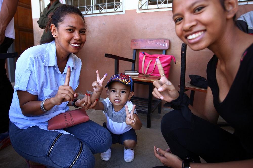 Após acompanhar a mãe e irmã a votar, uma criança mostra o dedo com tinta numa secção de voto para as eleições legislativas que decorrem hoje em todo o território de Timor-Leste. Díli, 22 de julho de 2017. NUNO VEIGA/LUSA