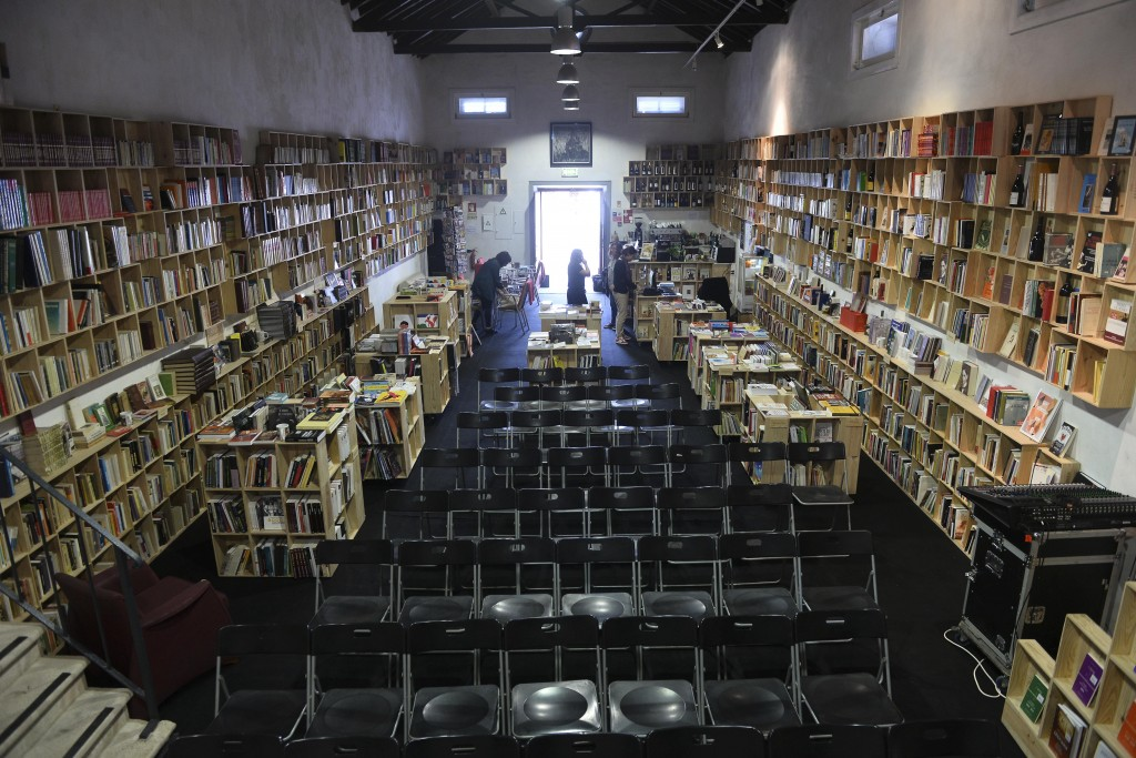 """Visitantes do Folio – Festival Internacional de Literatura de Óbidos observam livros numa antiga adega requalificada, onde a ordem é """"Ler devagar"""", tal como o nome da livraria ai instalada e onde, por se tratar de uma adega, se encontram centenas de livros ligados ao vinho, Óbidos, 15 de outubro de 2015. Começou hoje o """"Folio"""" Festival Internacional de Literatura de Óbidos, onde vários espaços são transformados em livrarias. CARLOS BARROSO/LUSA"""
