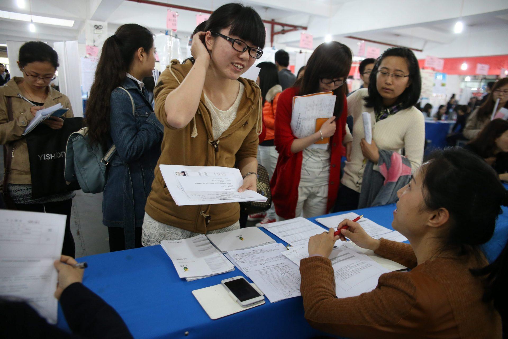 Foto LUSA: Uma estudante chinesa recém-formada à procura de colocação no mercado de trabalho. Hangzhou, província de Zhejiang, China, 28 de março de 2014. EPA / WU HONG