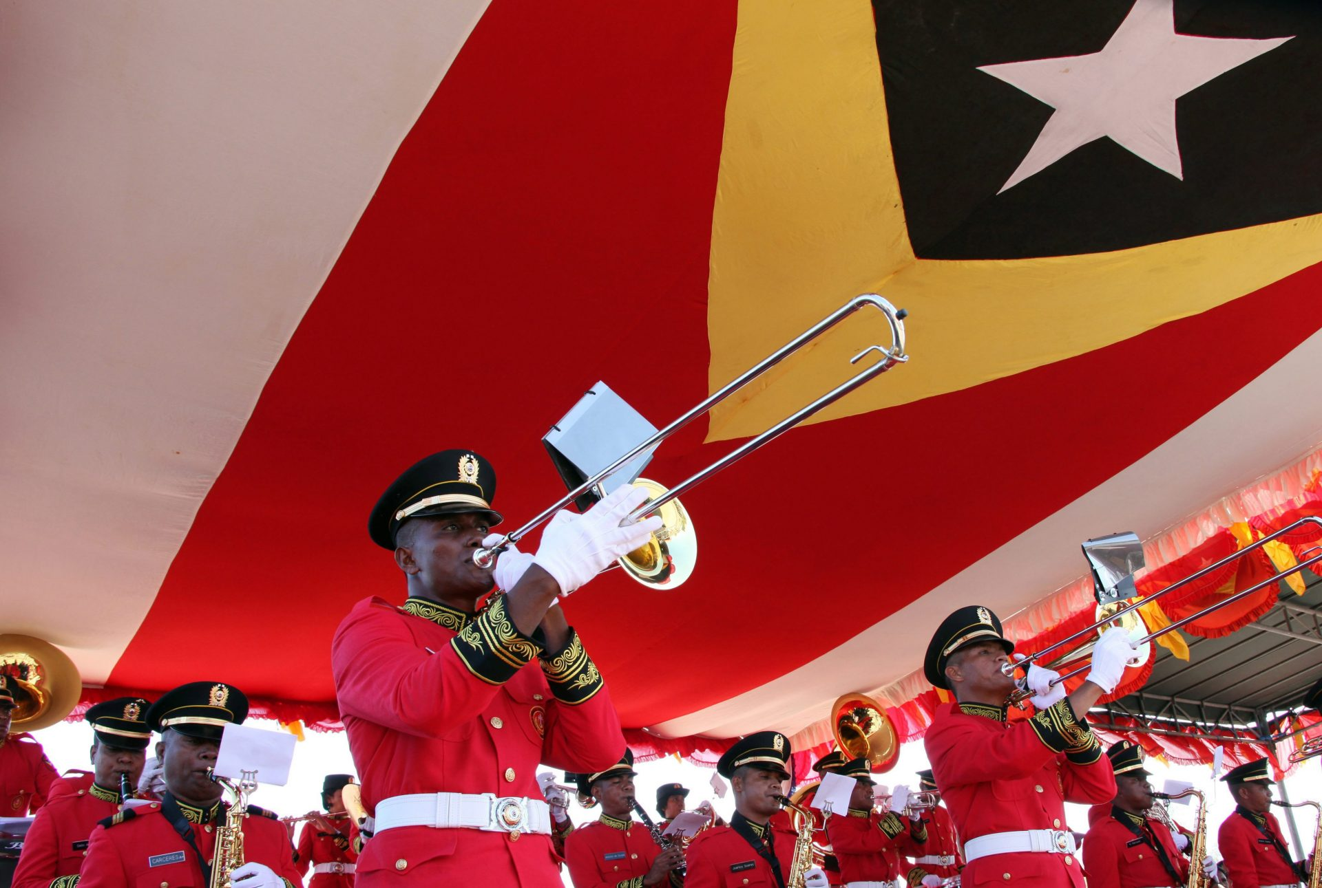 epa05045261 An East Timorese military brass band marches under a giant national flag during a parade to mark the restoration of their independence, in Dili, East Timor, also known as Timor Leste, 28 November 2015. East Timor was colonized by Portugal in the 16th century, until Portugal's decolonization of the country. In late 1975 East Timor declared its independence but was occupied by Indonesia that declared it as the country's 27th province the following year. In 1999, following the United Nations-sponsored act of self-determination, Indonesia relinquished control of the territory and East Timor became the first new sovereign state of the twenty-first century on 20 May 2002. EPA/ANTONIO DASIPARU