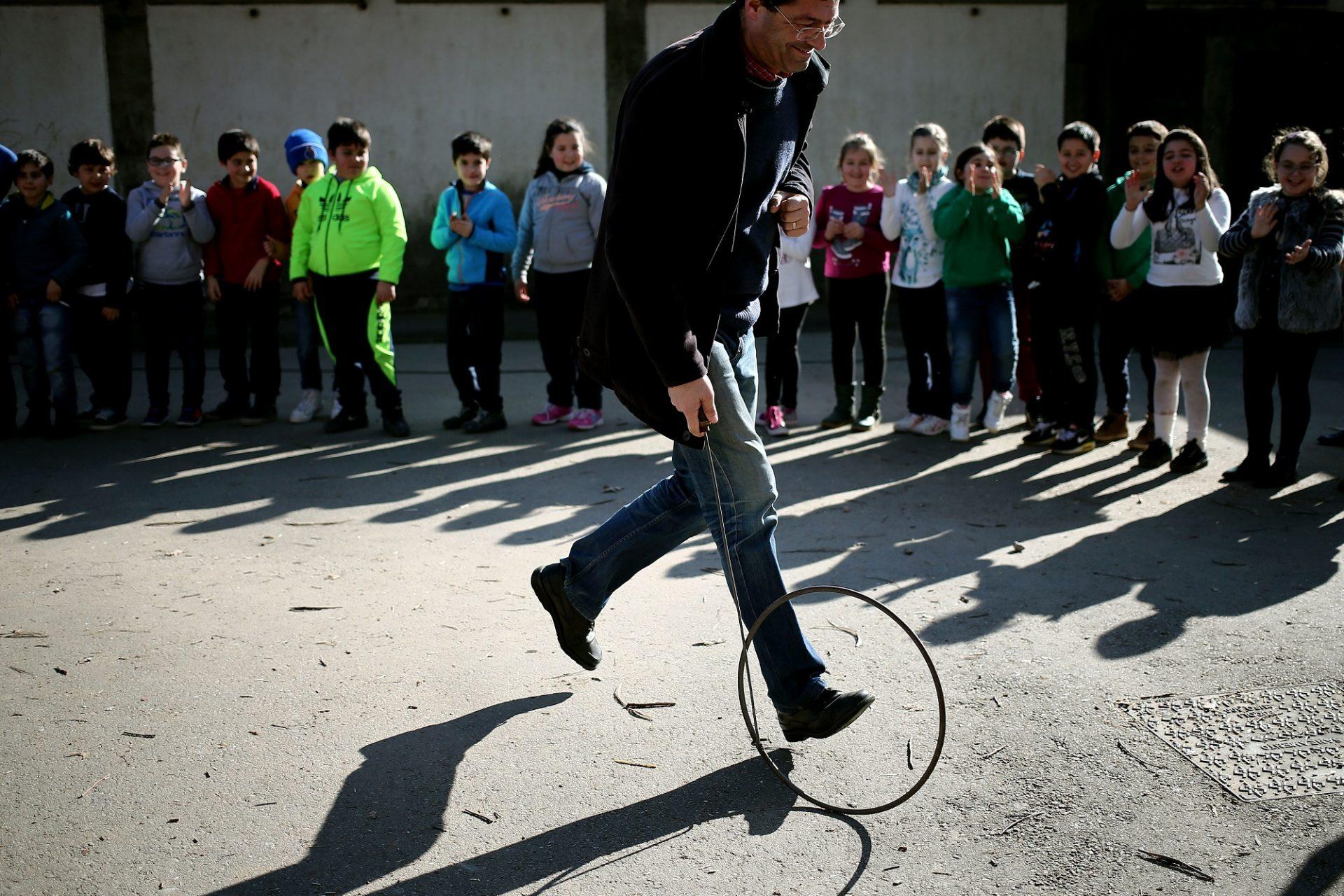 Um adulto demonstra como se brinca com o arco às crianças da escola do Susão que participam numa iniciativa da Associação das Coletividades do Concelho de Valongo para promover os jogos tradicionais portugueses junto das escolas do concelho de Valongo, 19 de fevereiro de 2016. ESTELA SILVA/LUSA