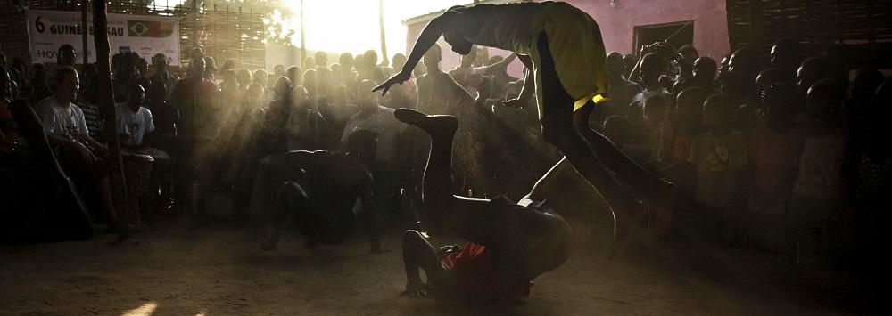 """Participantes treinam coreografia no espaço de ensaio do grupo cultural Netos do Bandim, durante a preparação do desfile de Carnaval de 2017, Bissau, Guiné-Bissau, 22 de fevereiro de 2017. O grupo conta com 120 pessoas, voluntários com gosto pela dança, mas os ensaios atraem também outros amigos """"dos bairros em redor - alguns até gostam e acabam por ficar no grupo"""". LUIS FONSECA/LUSA"""